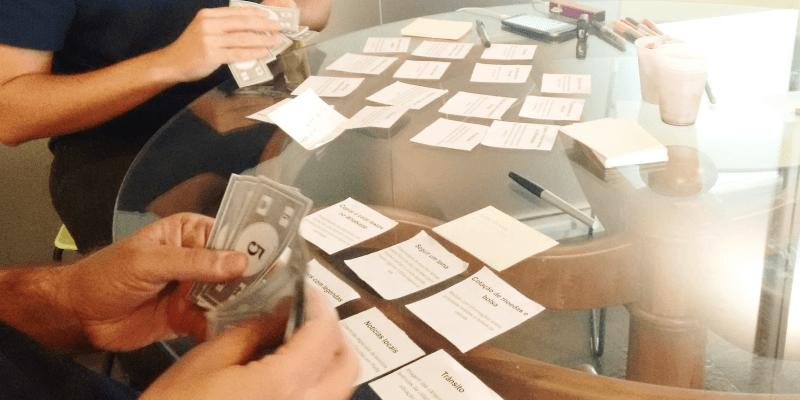 Um foco no detalhe das mãos de duas pessoas que estão mexendo em dinheiros de mentira, para avaliar o quanto pagariam por uma funcionalidade especifica para o portal da GauchaZH em um workshop de cocriação com usuários.